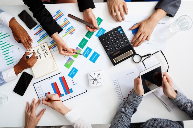 Zakenlieden handen op witte tafel met documenten en ontwerpen