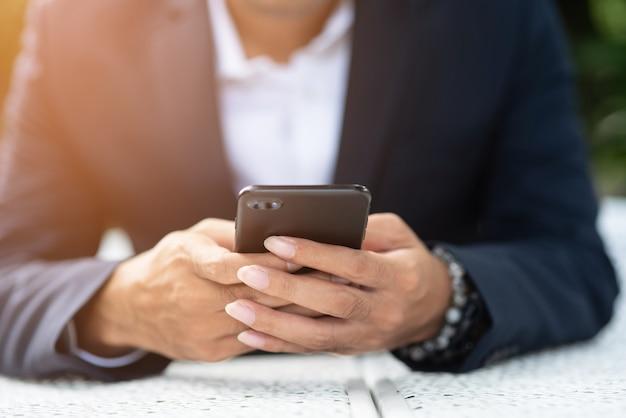 Zakenlieden houden de telefoon om e-mail op internet te controleren.