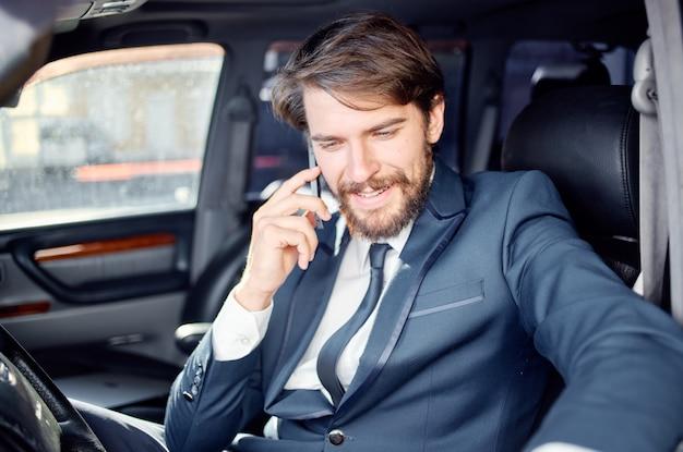 Zakenlieden in een pak in een auto een reis naar het werk communicatie via de telefoon