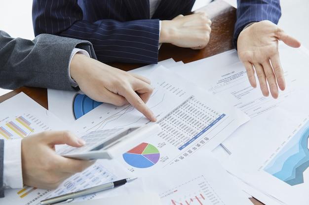 Zakenlieden in elegante pakken op een zakelijke bijeenkomst die berekeningen maken op kantoor