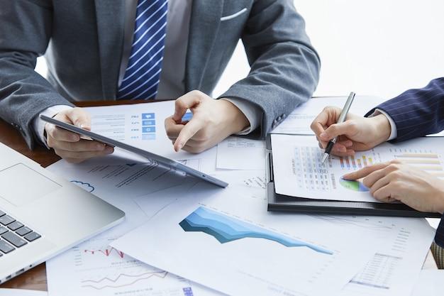 Zakenlieden in elegante pakken op een zakelijke bijeenkomst die een nieuw project op kantoor bespreken