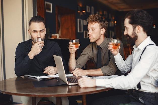 Zakenlieden in onderhandelingen. mannen met alcohol aan tafel zitten. vrienden praten.