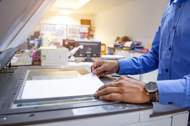 Zakenlieden scannen papieren op fotokopieerapparaat op kantoor werkplek.