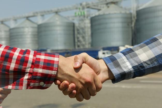 Zakenlieden schudden elkaar de hand tegen silo's. landbouwbedrijf