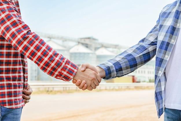 Zakenlieden schudden elkaar de hand tegen silo's