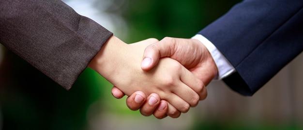 Zakenlieden schudden elkaar de hand, ze komen overeen om samen zaken te doen.