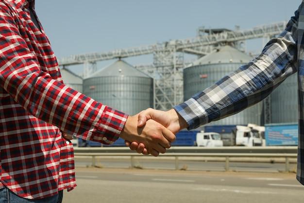 Zakenlieden schudden handen tegen silo's. landbouwbedrijf