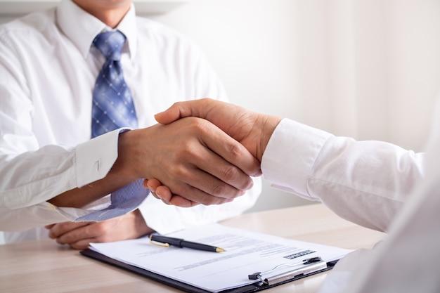 Zakenlieden slaan de handen in elkaar om nieuwe werknemers te werven om zich bij het bedrijfswerk aan te sluiten, komen overeen om mee te doen.