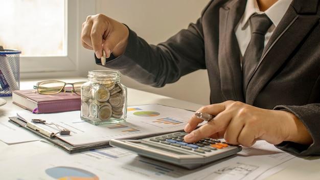 Zakenlieden stoppen munten in een spaarvarken om hun bedrijf te financieren.