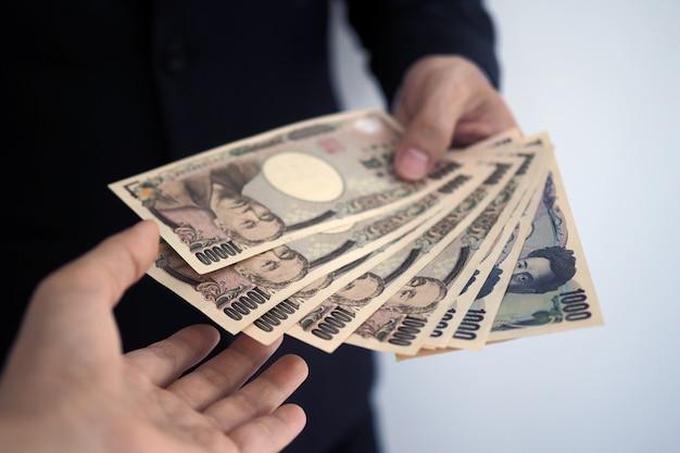 Zakenlieden sturen japanse bankbiljetten naar werknemers.