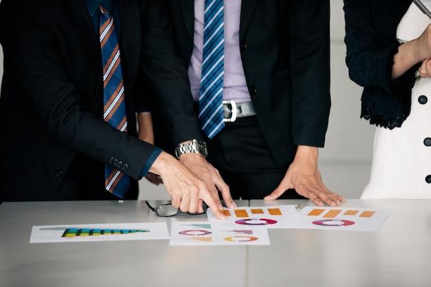 Zakenlieden werken en wijzen op grafiek financieel diagram en analyse documenten op kantoor tafel