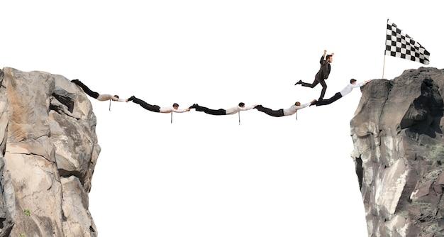 Zakenlieden werken samen om een brug te vormen tussen twee bergen om bij de vlag te komen. prestatie bedrijfsconcept doel