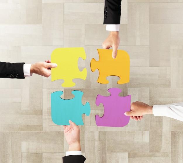 Zakenlieden werken samen om een gekleurde puzzel te bouwen