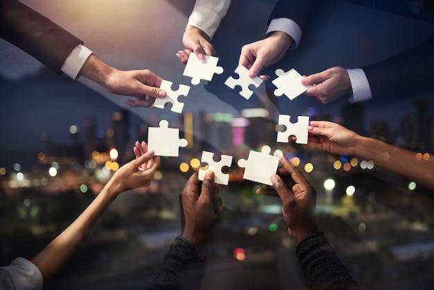 Zakenlieden werken samen om een puzzel te bouwen