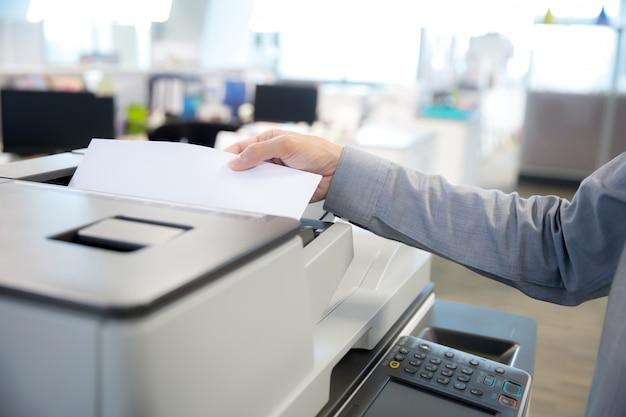 Zakenlieden zetten een papier op kopieerapparaten.