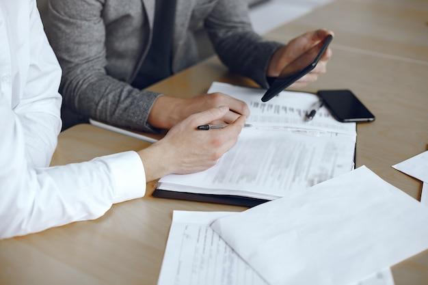 Zakenlieden zitten aan het bureau van de advocaat. mensen die belangrijke documenten ondertekenen.