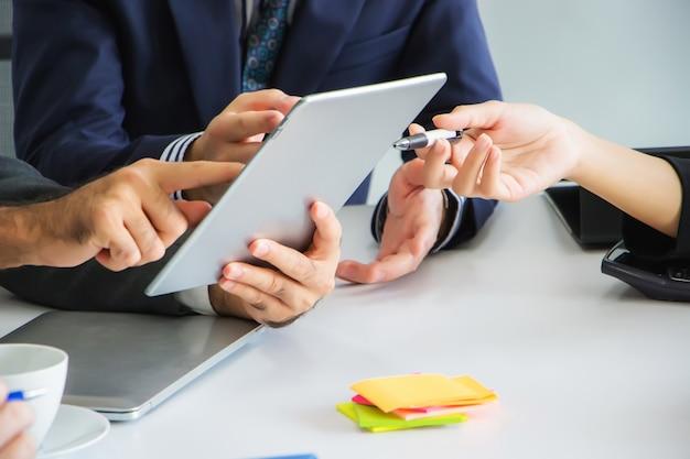 Zakenlieden zoeken en bekijken samen informatie op tablets om nieuwe projecten te creëren in de vergaderruimte op hun werkplek.