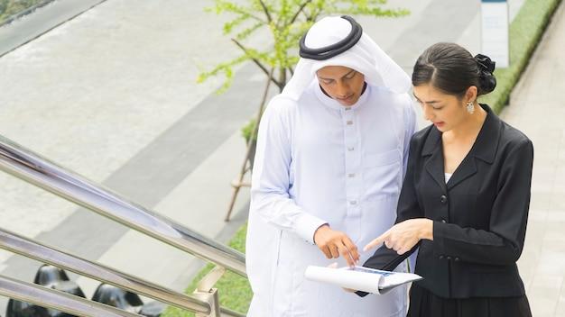 Zakenlui arabische man en vrouw praten en presenteren