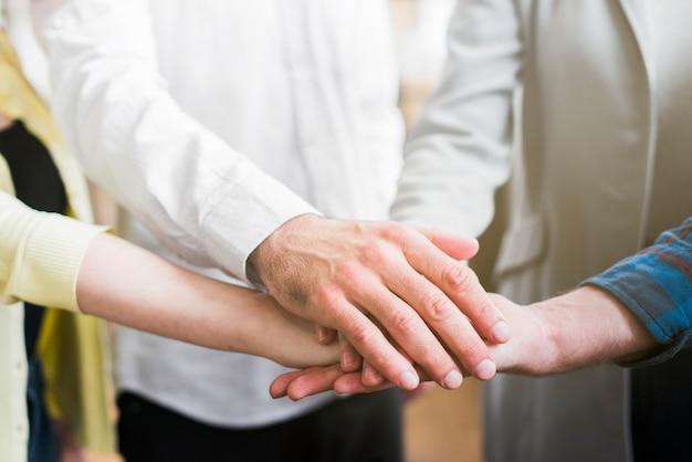 Zakenlui die hun handen stapelen om eenheid te tonen