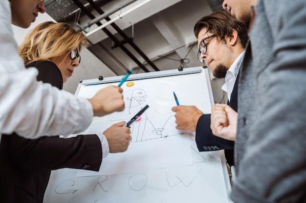 Zakenlui die met whiteboard strategie in een vergadering bespreken