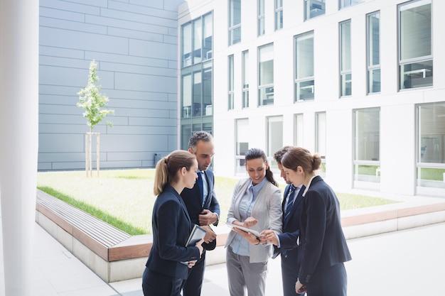 Zakenlui die over digitale tablet bespreken