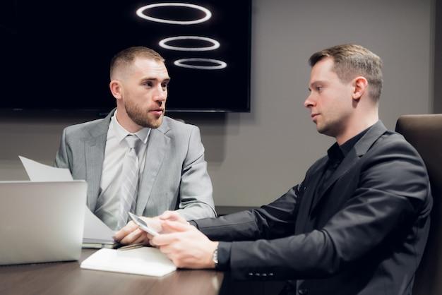 Zakenlui die samen in conferentieruimte tijdens vergadering op kantoor bespreken