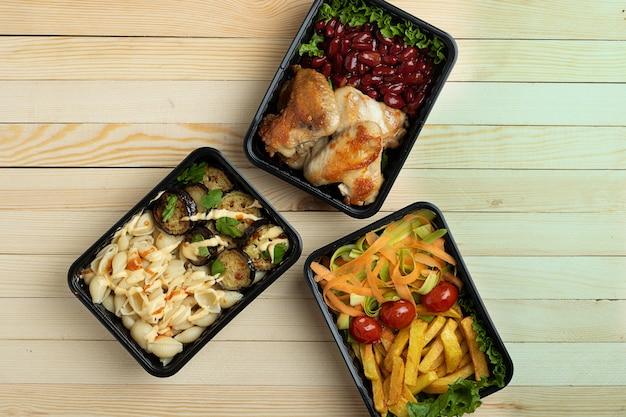Zakenlunch in voedseldozen, gebraden kippenvleugels, gestoomde groenten, gestoofd vlees, kant-en-klaarmaaltijd