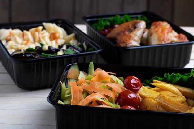 Zakenlunch in voedseldozen, gebraden kippenvleugels, gestoomde groenten, gestoofd vlees