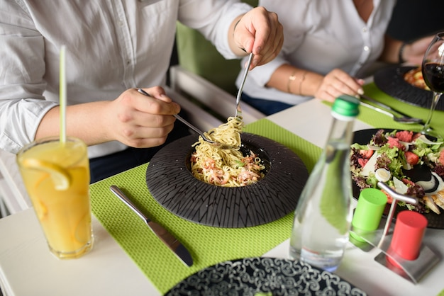 Zakenlunch italiaanse pasta voor groot gezelschap van collega's. lekker eten op de zwarte plaat. vrienden ontmoeten.