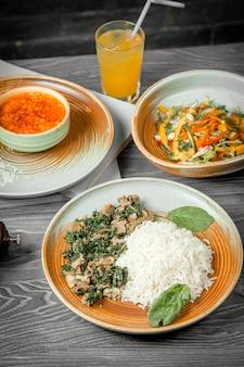 Zakenlunch kip spinazie met rijst soep kipsalade brood drinken en zwarte peper op tafel
