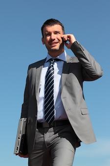 Zakenman aan de telefoon in blauwe hemel