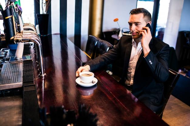 Zakenman aan de telefoon met een kopje koffie aan het loket in een bar