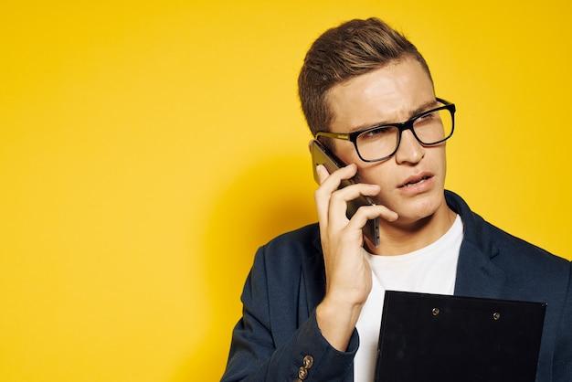 Zakenman aan het werk met een bril en een jas op een gele achtergrond