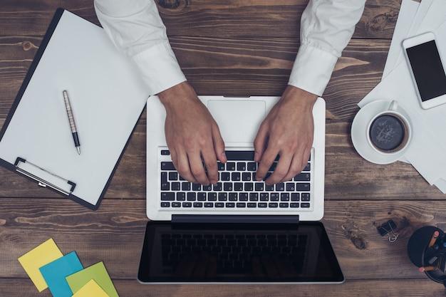 Zakenman aan het werk op kantoor met behulp van laptop