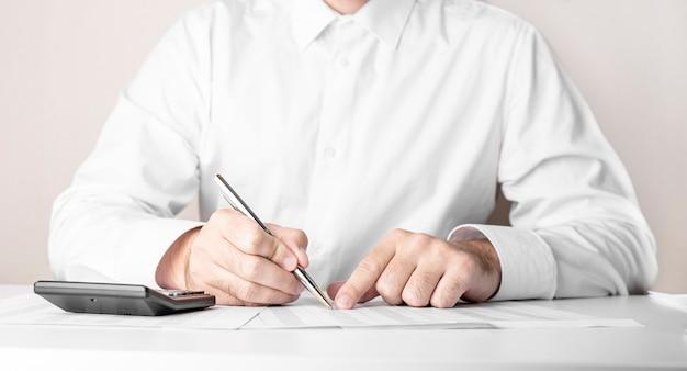 Zakenman aan tafel werken met pen en rekenmachine op wit