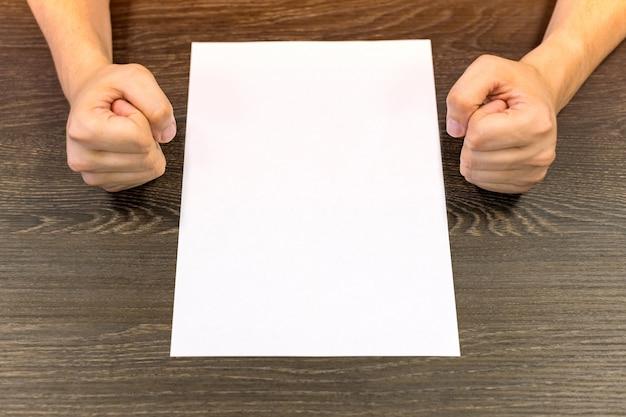 Zakenman aan tafel zitten. er staat een blanco vel papier op de tafel.