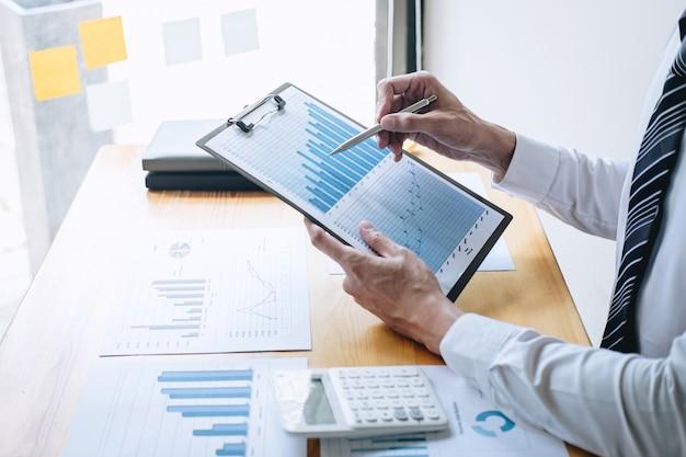 Zakenman accountant werken analyseren en berekenen kosten financieel jaarlijks financieel verslag balansoverzicht en analyseren document grafiek en diagram, financieren maken van aantekeningen op rapport