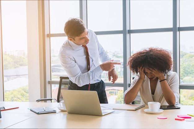 Zakenman als baas zijn werknemer de schuld geven en vermanen.