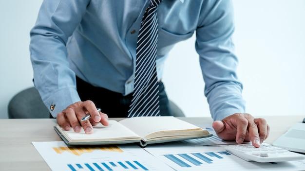 Zakenman analyseert de grafiek met laptop op kantoor voor het stellen van uitdagende zakelijke doelen en het plannen om het nieuwe doel te bereiken.