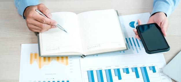 Zakenman analyseert de grafiek met smartphone op kantoor voor het stellen van uitdagende zakelijke doelen en het plannen om het nieuwe doel te bereiken.