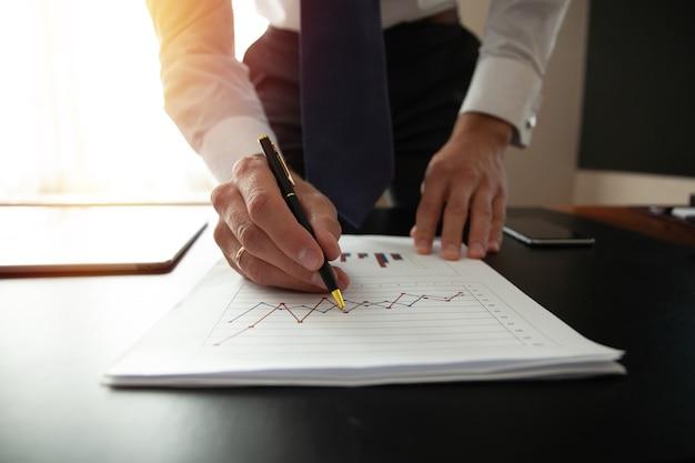 Zakenman analyseren investeringsgrafieken. boekhouding
