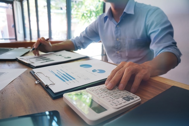 Zakenman analyseren investeringskaarten en druk op calculator knoppen over documenten. accounting concept