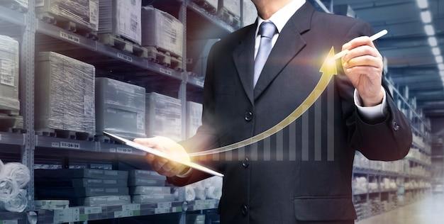 Zakenman beheert slim magazijn via internetcomputer toon winst, modern magazijn, distribueer netwerk bedrijfsconcept. zakenman gebruik tabletplan, controle van logistiek transport in magazijn