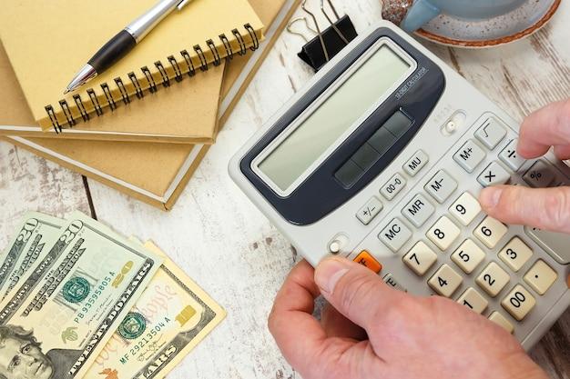 Zakenman berekent belastingen op een rekenmachine close-up