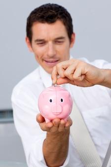 Zakenman besparingsgeld in een piggybank