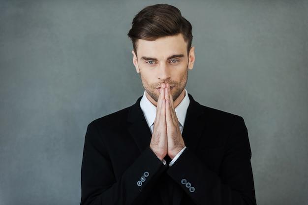 Zakenman bidden. nadenkende jonge man in formalwear hand in hand gevouwen in de buurt van gezicht