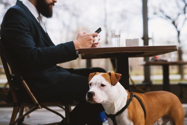 Zakenman bij coffeeshop met hond. beste vrienden in café.