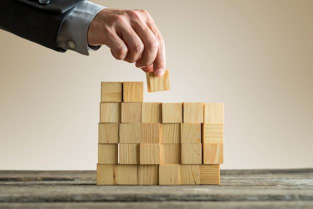 Zakenman bouwen van een structuur met houten blokjes op tafeloppervlak