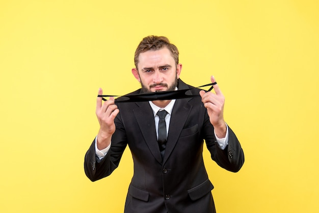 Zakenman buigen en houden zijn gezichtsmasker met zijn vingers op geel