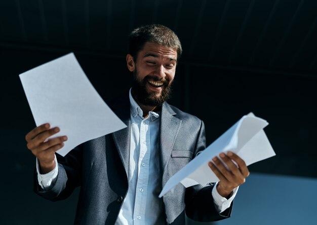 Zakenman buitenshuis met documenten in handen in de buurt van het bouwen van officiële levensstijl